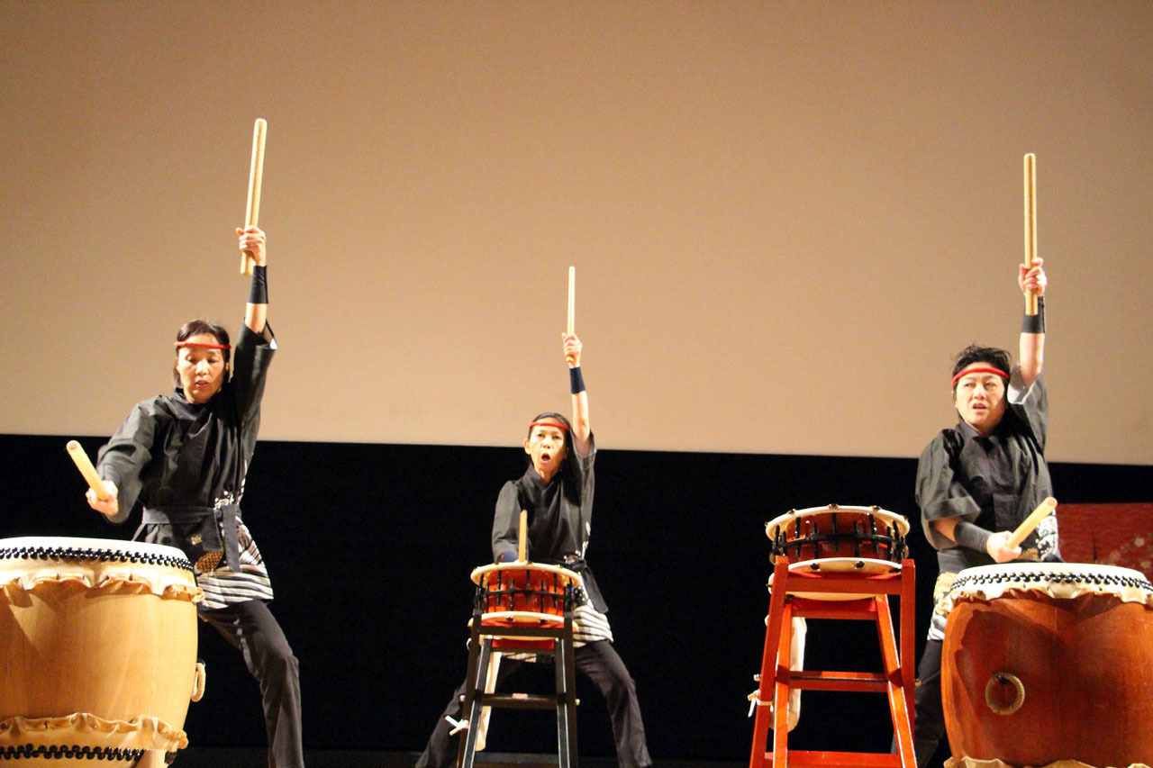 Three Taiko players on a stage