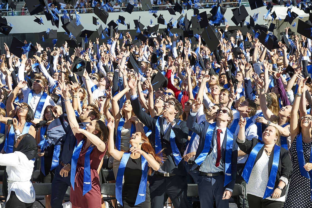 Graduates toss their caps in the air